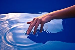 Hand Creating Ripples on Still Water
